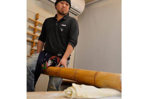日清亭の太い竹筒を使って麺を打つ様子